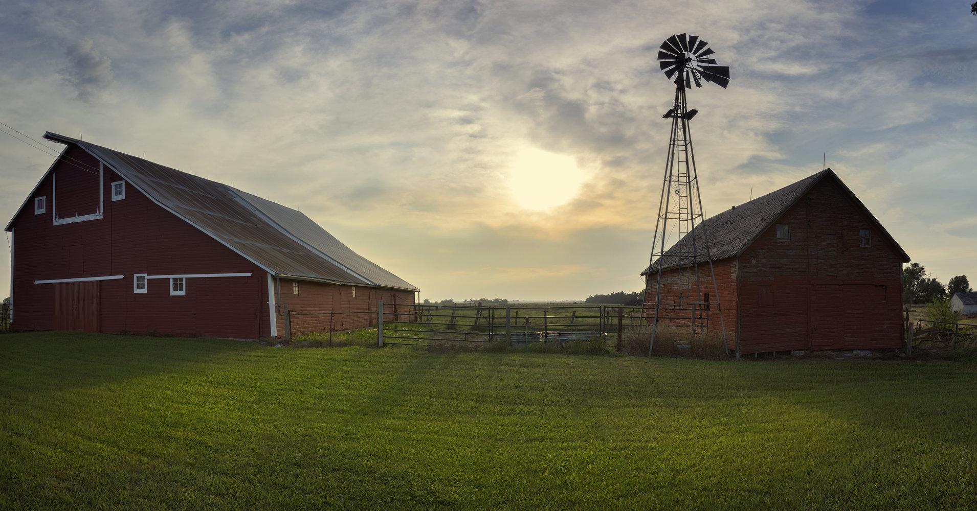 A barnyard with windmill set on the South Dakota plains at Sunset.