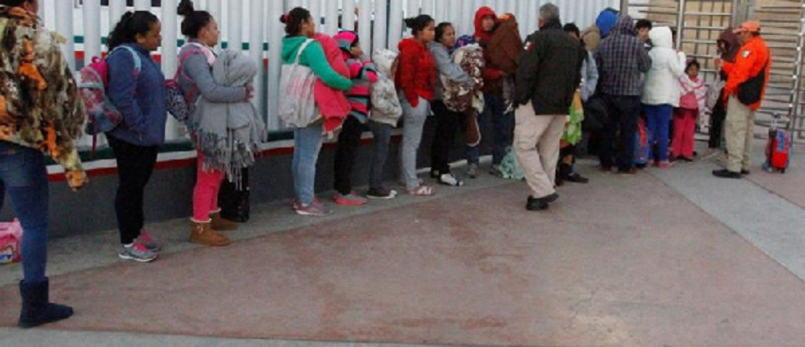 Immigrants from Central America and Mexican citizens queue to cross into the US to apply for asylum